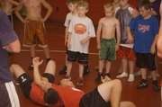Campers observe as Tonganoxie wrestling coach Jeremy Goebel and rising THS senior Jeremie Maus demonstrate a move on the mat on Wednesday, June 10 at Tongie Kids Wrestling Camp of Champs.