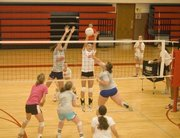Jenny Whitledge and Kailin Kuzmic extend for a block during action at Tonganoxie High volleyball camp on June 24.