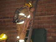 One of the men carries a dummy victim down the ladder during the Fairmount Township Fire Department training session.