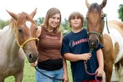 Ashley and Brandon Williams hold on to their horses Sheba, left, and Dallas. Ashley said this year at the fair she will be focusing primarily on her horse. Brandon will also be focusing on his horse, but he will be showing two pigs as well.