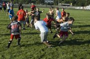 A swarm of youth football campers converge in the backfield during a scrimmage on Thursday at Tonganoxie High's Beatty Field.