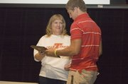 Lisa Elliott, mother of Tonganoxie High student Jeremy Elliott, who died in April, presents Jeremie Maus with the Elliott Heart Award on Thursday at Chieftain Power Awards Night.