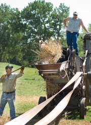 Two men use a steam engine to thresh some wheat during the McLouth Threshing Bee.