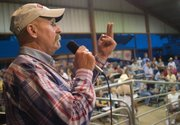 The auctioneer verifies the number of a winning bidder.