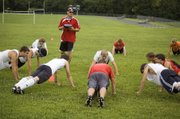 Tonganoxie soccer seniors surround assistant coach Brian Kroll during stretching at the beginning of practice on Monday.