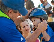 Christina Smith watches Tonganoxie Recreation Commission Director Gayle Parker fit a helmet on to her son Mcclellan Smith's head. About 50 free helmets were given out and properly fitted to area children who participated in the Safe Routes to School bike rodeo.