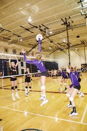 Baldwin High School junior Lyndsey Lober, center, spikes a ball during the Bulldogs' match against Bonner Springs Tuesday night.