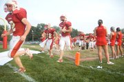 Jeff Sims, Jeremie Maus, Ben Myers, Dylan Scates and Billy Anderson run past a line of THS cheerleaders, onto Beatty Field for Tonganoxie's homecoming game against Osawatomie.