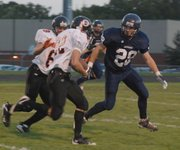 Bonner Springs' Lucas Porras (22) looks for room to run as Mill Valley's Dylan Floyd (28) closes in to make the tackle.