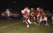 DJ Lindsay protects the ball as he breaks outside for an 80-yard touchdown run in Tonganoxie's 75-12 beatdown of Santa Fe Trail on Friday night at Beatty Field.