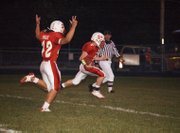 Jeremie Maus throws up his arms to signal a touchdown as Jeremy Carlisle crosses the goal line for Tonganoxie High in the first quarter of the Chieftains' 75-12 drubbing of Santa Fe Trail on Friday night.