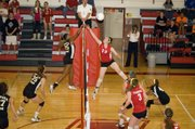 Maggie Franiuk challenges a Topeka player at the net during Tonganoxie's best-of-five victory on Thursday night.