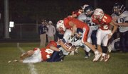 Jason Espeland and Justin Jacobs engulf a St. James Academy ball carrier during Tonganoxie High's 40-28 non-conference win on Friday night at Beatty Field.