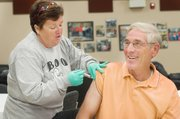 Pat Deaver, with the Douglas County Visiting Nurses, Rehabilitation and Hospice Care Association, gives Jerry Bailey a seasonal flu shot Friday at the Tonganoxie High School.