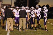 Baldwin High School football coach Mike Berg, center, talks to a group of his players during a timeout Friday night.