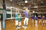 Baldwin High School freshman Monica Howard goes up for a spike over two De Soto players Saturday.