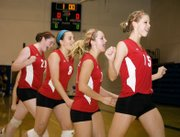 Tonganoxie High volleyball players Maggie Franiuk, Danielle Miller, Hannah Kemp and Brooklyn Kerbaugh run off the floor celebrating moments after defeating Bishop Ward in pool play at the Kaw Valley League tournament to earn a spot in the semifinals on Saturday at Perry.