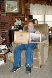 Jack Richtor, Pomona, who served in the Navy during the Korean War, displays a certificate of an operation in which he was involved and a picture of his battleship.