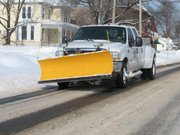 A snow-plowing truck makes its way down 155th Street Thursday in Basehor.