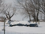 Snow piles up around a car parked next to a 163rd Street home in Basehor.