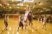 Tonganoxie High senior forward Justin Jacobs skies for an offensive rebound in the second quarter of the Tonganoxie Invitational title game against Silver Lake on Saturday. The Chieftains lost in overtime, 46-43.