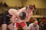 Tonganoxie High freshman Britton Price (135 pounds) holds his Lansing opponent in a headlock on Thursday at THS. The Chieftains lost two home duals, to LHS and Bonner Springs.