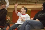 Shane Lewis cheers wildly after watching Jonas Myers win a wrestling match on Feb. 4. Shane, a second-grader at Tonganoxie Elementary School, met Myers through a program that sends Tonganoxie High students to the elementary school to work with and mentor young students.
