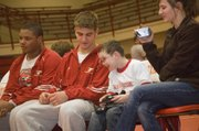 Tonganoxie High sophomore Jonas Myers and Tonganoxie Elementary second-grader Shane Lewis talk on the THS wrestling bench during a home event on Feb. 4. Lewis watched all of the matches from the bench while serving as the team's water boy.