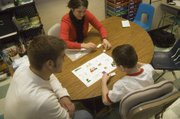 "Tonganoxie Elementary School second-grader Shane Lewis works on a reading exercise in the resource room with the help of Tonganoxie High sophomore Jonas Myers and his teacher, Shelby Noonan. Myers, who takes the THS ""Leadership in Sports"" class, helps Shane with his work one morning each week."