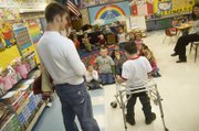 """Students in Tiffany Parker's kindergarten class listen attentively as Tonganoxie Elementary School second-grader Shane Lewis introduces them to his friend Jonas Myers, a Tonganoxie High sophomore. Myers works with Shane each week at TES through the THS """"Leadership in Sports"""" class."""