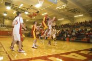 Jeremy Carlisle gets whacked in the air Tuesday night against Atchison. It was THS, however, thad did most of the thumping in a 74-48 first-round sub-state victory.