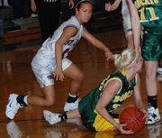 Basehor-Linwood senior Cassy Bever gathers a loose ball as St. James Academy senior Megan Spradlin closes in during the first quarter Thursday. BLHS beat St. James, 53-37, in the substate semifinals.