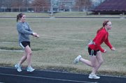 Hannah Kouri, left, holds on as Annie Beck, right, runs resistance sprints during a recent track practice in Eudora.