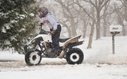 Matt McCoy rides around on an ATV during Saturday's snow storm.