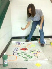 Emily Hall, artistically splatters paint on her blood drive sign Wednesday.