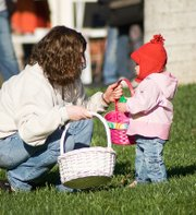Susan Ross, helps her daughter Elizabeth Ross, 18-months, during the Easter egg hunt.