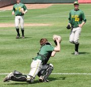 Basehor-Linwood catcher Jayce Rymer makes a diving catch in foul territory during the first inning against Bishop Ward as pitcher Tyler Henley looks on.
