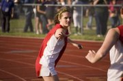 Tonganoxie High senior Andie Jeannin reaches out for the baton held by 4x800 relay teammate Sagan Scates. The Chieftains' girls 3,200-meter relay team won first place Friday at the Bobcat Relays, helping THS to a team title.