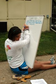 A volunteer transfers a to-do list to an dry-erase board.