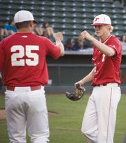 THS assistant coach Mitch Loomis greets Chieftains starting pitcher Brandon Yoder with a fist bump after Yoder worked out of a bases-loaded jam against Bonner Springs in the fifth inning Friday at CommunityAmerica Ballpark.