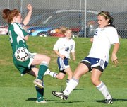 Mill Valley's Jenna Wells unleashes a shot that sailed wide thanks to a challenge by Basehor-Linwood's Christina Self.