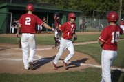 Tonganoxie High sophomore Austin Harkrader is congratulated by teammate Ethan Lorance after scoring as a pinch runner in the fifth inning of the Chieftains' 6-4 loss to Jeff West on Tuesday.