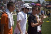 """DJ Lindsay, Austin Stone, Jeremy Carlisle and Bret Koch walk around the Cessna Stadium track during a """"Champions Lap"""" ceremony at the state track meet in Wichita on Saturday."""