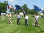 The Basehor VFW Memorial Day service begins with Trustee Wilbur Grisham in the lead carrying the American flag.