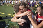 Andie Jeannin is congratulated by Jeremy Carlisle, Abby Eisman and other Tonganoxie High teammates after winning the Class 4A state championship in the 800 on May 29 at Wichita.