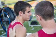 Disappointed about being held out of the 4x400 state championship race, Tyler Woolworth gets a pat on the back from teammate Jeremy Carlisle moments after Tonganoxie finished third in the race.