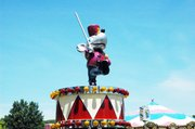 An animated mouse sits atop one of the carnival rides, waiting for screaming youngsters.