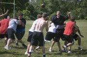 Tonganoxie High defensive lineman Bryson Hewins yells in an attempt to distract Chieftains quarterback Jeremy Carlisle on a pass attempt Friday morning at THS football camp.