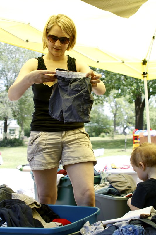 "Sara Miller of Eudora checks the size of a pair of shorts for her son Andrew at Denise Porras' garage sale in De Soto on Friday afternoon. Miller returned to the garage sale a second time, ""This morning I just bought my son shorts for the summer but everything was such a great deal I came back to stock up on bigger clothes for the winter."""