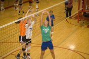 Former Kansas University volleyball player Emily Brown gets underneath the ball for a set as Tonganoxie campers Kailan Kuzmic and Katelyn Waldeier close in on the opposite side.